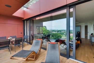 """Sofistikované bydlení v kopci aneb dům se skleněnou """"hlavou"""" - Obývací prostor a terasa v prvním patře. Velké posuvně zdvižné dveře ze systému Schüco ASS 70.HI v šířce 6,44 m a výšce 2,67 m. Prosklená část střechy zajišťuje dostatečný přísun světla."""