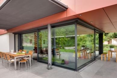 """Sofistikované bydlení v kopci aneb dům se skleněnou """"hlavou"""" - Transparentní prostor kuchyně a kryté terasy v přízemí. Konstrukčně jde o kombinaci posuvného systému Schüco ASS 70.HI s pevnými částmi z fasádního systému Schüco FW 50+.SI."""