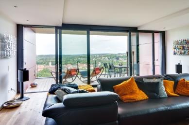 """Sofistikované bydlení v kopci aneb dům se skleněnou """"hlavou"""" - Hliníkové profily v odstínu šedá mat TIGER s metalickou texturou barevně ladí s červenou fasádou, bílými stropy a zdmi, dřevěnými masivními prkny i šedými deskami z čediče na podlaze."""