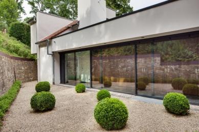 """Sofistikované bydlení v kopci aneb dům se skleněnou """"hlavou"""" - Přechod k původní, v roce 1987 renovované, budově (sousedící zleva). Ta nabízí dalších 120 m2 prostoru pro hosty a rodinu. Plochy s pevným zasklením (Schüco FW 50+.HI v rozměru 10,71 x 2,5 m) i prosklené dveře do objektu vnášejí dostatek denního světla."""