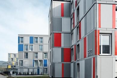 Modulární stavební konstrukce s úspornými okny Schüco Alu Inside, která přispívají k prakticky nulovým nákladům za topení a teplou vodu - Jednotlivým budovám je přiřazeno primární barevné značení - žluté, modré a červené. Pospolitost venkovní fasády vyjadřují odstupňované šedé tóny. - foto: Schüco International KG a LiWooD, München