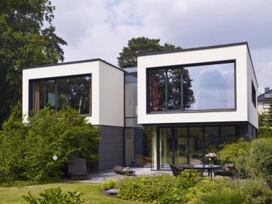 """Rodinný dům s """"terasovitým"""" interiérem a výhledem na jezero - Projekt rodinného domu vychází z požadavku klienta prostory co nejvíce otevřít směrem k jezeru. Nerušený výhled zprostředkovávají úzké okenní a fasádní profily Schüco - foto: Foto kredit Schüco International KG"""