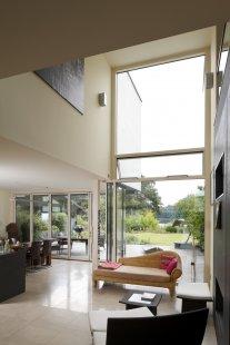 """Rodinný dům s """"terasovitým"""" interiérem a výhledem na jezero - Obývací prostor s přístupem na terasu a výhledem na jezero. Automaticky řízená ven výklopná okna a střešní okna pro příčnou ventilaci v létě (Schüco AWS 102 and Schüco AWS 57 RO). - foto: Foto kredit Schüco International KG"""