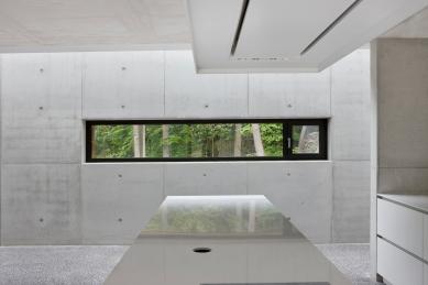 Rodinný dům zasazený do přirozeného prostředí vyrostl v Belgii - Pohledový beton je dominantním prvkem interiérového designu. Vidět je z části otvíravý okenní element ze systému Schüco AWS 75.SI. - foto: Laurent Brandajs