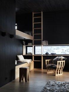 Bludný kámen poskytuje soukromí ivýhledy na vrcholky hor - Kontrasty světel, materiálů a barev: Úzká horizontální i vertikální okna přerušují černé dřevěné obložení interiéru. - foto: Invit Arkitekter, Ålesund / Johan Holmquist