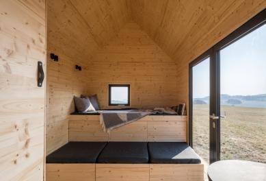 Designový domek Mobile Hut má kola, jezhliníkového plechu, ale ctí archetypální tvar českého domu - Pomocí polohování vestavěného nábytku se může přizpůsobit dispozice různým funkcím, na vyvýšeném lůžku v přízemí s dvěma řadami výsuvných šuplíků se po rozložení vyspí dva lidé (horní řada zásuvek jsou úložné prostory) a nahoře v patře nad plně vybavenou kuchyňkou je ještě manželská postel.
