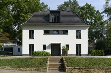 Renovace rodinného domu v německém městě Bergisch Gladbach - Pohled z ulice: Symetrické uspořádání oken a dveří strukturuje fasádu i střechu.  Opakuje se zde motiv úzkých, vertikálně orientovaných dvoukřídlých oken (Schüco AWS 75.SI).