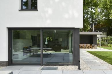 Renovace rodinného domu v německém městě Bergisch Gladbach - Přechod mezi zahradou a domem tvoří betonové desky a rýnský štěrkopísek. Tmavé rámové profily prosklených ploch kontrastují se světlými povrchy.