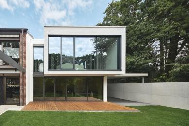 Soukromý dům v německém Gersthofenu ve stylu Miese van der Rohe - Fasáda orientovaná do zahrady: velkoformátové prosklené plochy s úzkými profily, které jsou harmonicky rámovány omítnutými částmi objektu. Horní patro je z dřevěných trámů. - foto: Christian Eblenkamp