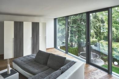 Soukromý dům v německém Gersthofenu ve stylu Miese van der Rohe - Obývací prostor v horním patře: Prosklené elementy na výšku místnosti, z nichž jeden lze otevírat, umožňují maximální přísun světla a výhled do zahrady (Schüco FWS 35 PD.SI). - foto: Christian Eblenkamp
