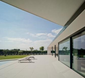 Posuvná fasáda, která respektuje náladu obyvatel - Venku i uvnitř je dlažba ze světlého přírodního kamene, která vizuálně propojuje a sjednocuje venkovní a vnitřní prostory. - foto: Schüco International KG / David Frutos