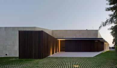 Posuvná fasáda, která respektuje náladu obyvatel - Při pohledu ze severní strany s příjezdovou cestou a hlavním vstupem budova působí uzavřeně a nenápadně. Žaluzie z irokového dřeva a reliéfní obklady z přírodního kamene tvoří materiálové i barevné kontrasty. - foto: Schüco International KG / David Frutos
