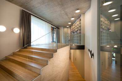 Dům, který se na dotek otvírá majitelům ipřírodě - Interiérový minimalismus z nábytku na míru v barvě bílé kávy, šedých pohledových betonů a dubových podlah.