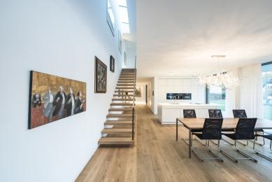 Když se potkají představy architekta aklienta - Rozdělení a uspořádání obou podlaží je dokonale přizpůsobeno svažitému pozemku nemovitosti. Samonosné schodiště vede ze vstupního prostoru (v přízemí, na straně orientované do ulice) dolů do hlavních obytných prostor na úrovni zahrady. - foto: Olaf Herzog