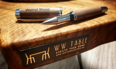 Značení pro nábytek 9× jinak: Designové, elegantní, odolné - 3D hliníkové štítky pro výrobky firmy Walnut Wood Table ukazují, že v jednoduchosti je krása. Celoplošná černá struktura štítku spolu<br>s vystupující zlatě lesklou ražbou podtrhují jedinečnost dřeva, ze kterého jsou stoly vyrobeny.