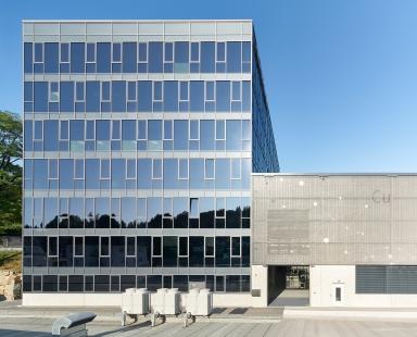 Systémy Schüco na nové kancelářské budově a výrobní hale: Samozatmavovací sklo a potištěná textilní fasáda - Nová výrobní hala navazuje přímo na prosklenou kancelářskou budovu. Je opatřena předsazenou textilní fasádou Schüco FACID 65. Plášť kancelářské budovy je plně prosklený ze sloupko-příčkové fasády Schüco FWS 60.HI s pevnými prvky a větracími otvíravo-sklopnými okny Schüco AWS 75 BS.HI. Integrované dvojité izolační sklo je vyrobeno z elektrochromatického skla SageGlass® od společnosti Saint-Gobain. - foto: Christian Eblenkamp