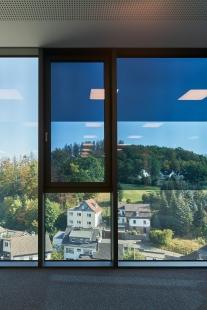 Systémy Schüco na nové kancelářské budově a výrobní hale: Samozatmavovací sklo a potištěná textilní fasáda - Okna na celou výšku místnosti s elektrochromatickým sklem SageGlass® od společnosti Saint-Gobain jsou rozdělena do tří individuálně ovládaných zón. To lidem umožňuje pracovat kdykoli během dne bez oslnění a užívat si optimální denní světlo za všech povětrnostních podmínek. - foto: Christian Eblenkamp