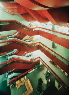 """Dům bytové kultury vPraze, otázky vztahu architektonické ideje a komerční praxe - Přehledný koncept původního řešení atria sjeho přístupným """"pobytovým"""" dnem. Komplexní barevné řešení – tzv. chilli červeň zevnitř objektu (do exteriéru prostupující podhledy, zábradlí, eskalátory a rámy oken), kontrastuje s temným obkladem zpředzvětraného plechu vexteriéru a pohledovými betonovými stěnami vinteriéru. - foto: Jaroslav Franta - fotografie z počátku osmdesátých let"""